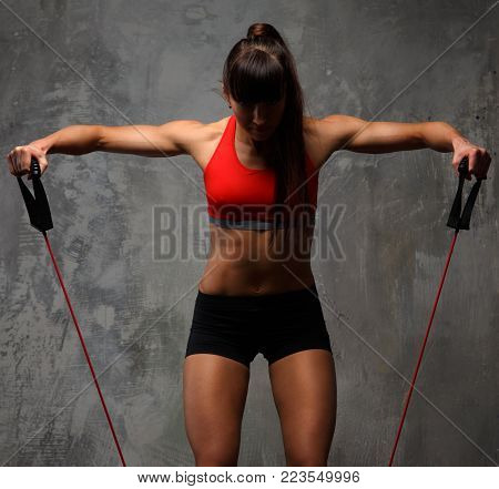 Fitness woman in sportswear doing exercises with expander on grey background