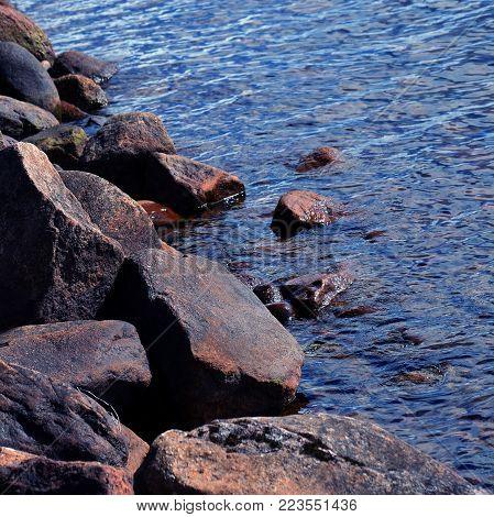 Rocky seashore on summer. Square shape image.