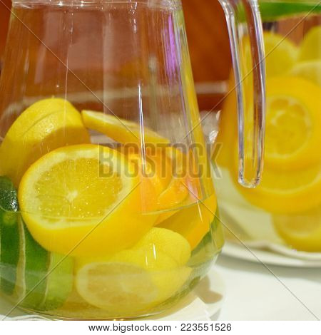 Water with orange and lemon in glass jug.