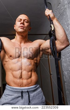 Strong muscular man bodybuilder poses and shows his abs