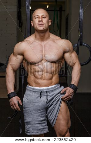 Strong muscular man bodybuilder poses and shows his muscles