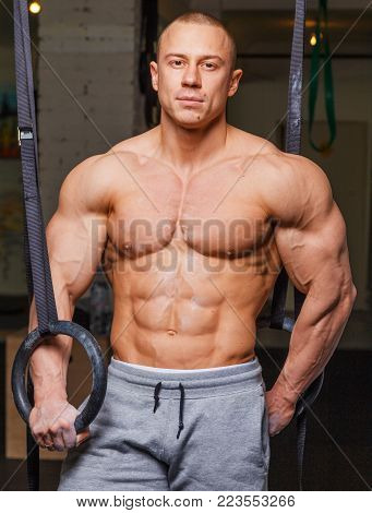 Strong muscular man bodybuilder poses and shows his body