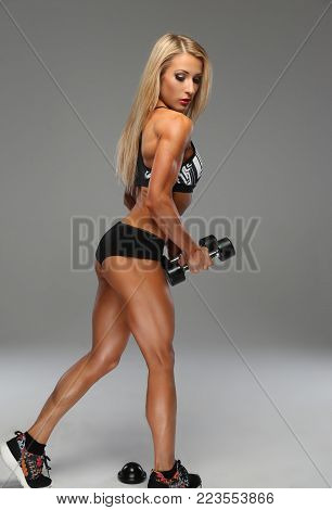 Athletic blond woman posing with dumbells ober grey background.