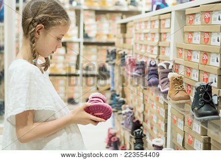 Little girl choosing winter shoes in the mall.