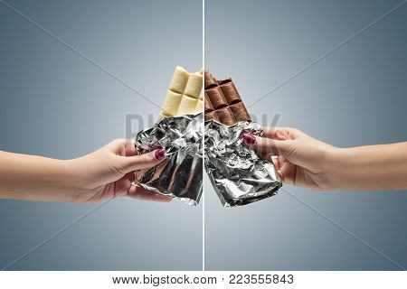Hands of a woman holding a tiles of brown and white chocolate against the studio. concept of confrontation, differences in taste and preference