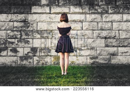 Young beautiful girl hugged her arms around her waist and stands face to the wall. The concept of peace of mind and balance. A single confrontation with the external hostile world. Hope only for yourself