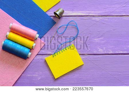 Basic blanket stitch. How to do a basic blanket stitch. Wool or synthetic felt sewing for kids. Colourful felt sheets, thread set, thimble on a wooden background with copy space. Top view