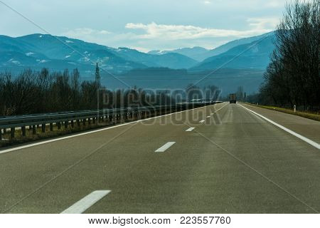 Two line wide highway on a cloudy winter day leading to the mountains