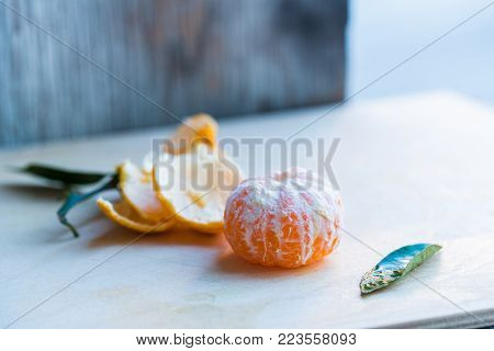 CloStudio image of peeled ripe juicy tangerine and its peel on white wooden board
