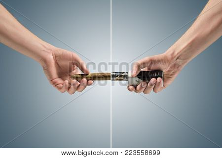 Hand holding an electronic cigarette and unlit cigar at studio. concept of confrontation, differences in taste and preference