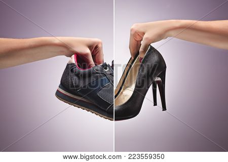 Hand Holding Old Dirty Sneaker Shoes and fashionable high-heeled female shoes. Concept of confrontation, differences in taste and preference