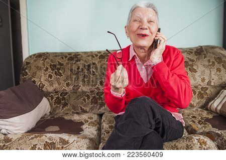 Senior old woman laughing sincerely to a conversation she's having over her phone