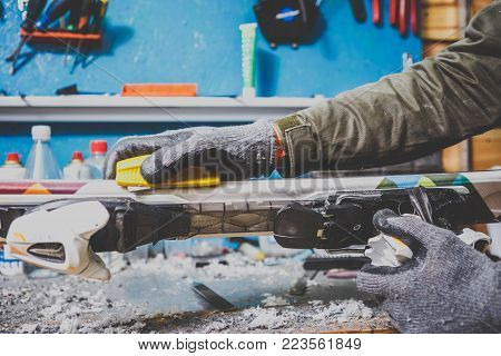 Male worker repairing Stone, edge sharpening in ski service workshop, sliding surface of the skis. sharpening of an edging of a mountain skis by means of the individual tool. Theme repair of ski curb.