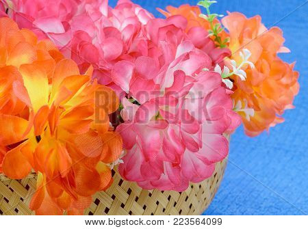 Bouquet in a basket of Artificial flower rose peony red white yellow and orange bright color made of synthetic fabric and plastic. Flowers lie on the table on blue fabric. Objects close up.