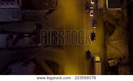 Evening road traffic. night illumination. Aerial drone from above view to moving cars. Aerial vertical view at night of city traffic illuminated by city streets and skyscrapers.