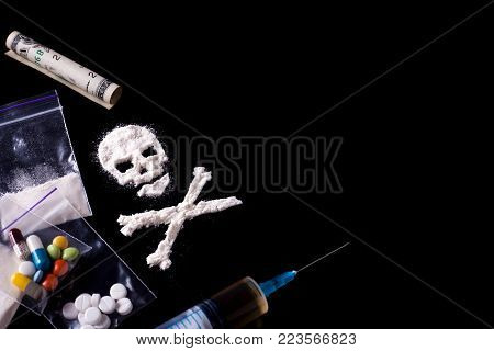 Drug dependence Kills. A line of cocaine in the form of a skull and a roll of a dollar, sachets with a dose, pills, syringe. Black background. Addiction concept. Copy space for text