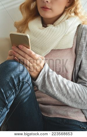 Young woman resting at home and resding text messages in her smartphone