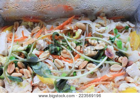 Pad Thai (Phad Thai) Stir-Fried Rice Noodle Dish Close Up. Asian Food Cooked with Chicken, Tofu, Egg, Vegetables and Nuts. Healthy Organic Meal in Take Out Box. Fresh Traditional Noodle Thai Food.