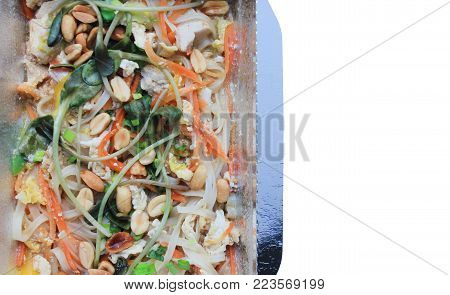 Pad Thai (Phad Thai) Stir-Fried Rice Noodle. Asian Food Cooked with Chicken, Tofu, Egg, Vegetables and Nuts. Healthy Organic Meal in Take Out Box Isolated on White. Fresh Traditional Noodle Thai Food.