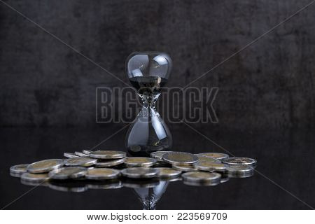 Long term investment or financial time counting down concept, sandglass / hourglass with coins on black table and black cement loft background.
