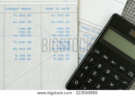 Office salary slip for tax and debt calculation concept by salary revenue slips with numbers and calculator put on table, year to date tax declare.