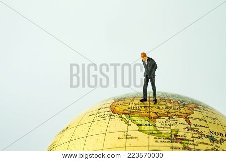 miniature people figure businessman standing on united states of america map on globe as world leader decision concept.