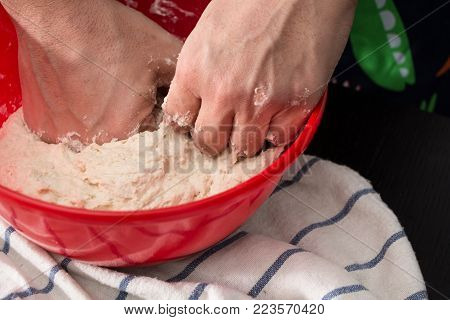 Male Hands Kneading Dough In Red Bowl, Baking Preparation Closeup.