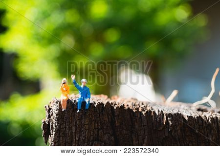 Miniature people, lover sitting chill out on green nature background using for holiday concept