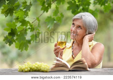 Mature woman with glass of wine and bunch of grapes reading book at the table