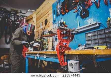 A man in work clothes repairman in the workshop ski service repairing the sliding surface of the ski at Ski vise. In the hands of a tool. Theme ski repair and maintenance of equipment.
