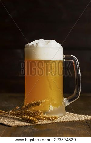 Beer with foam in a misted mug on a wooden surface. Alcoholic unfiltered drink in a glass on a bag with spikelets.