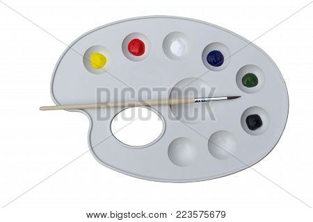 new palette with paints and one tassel on white background close-up, top view, flat