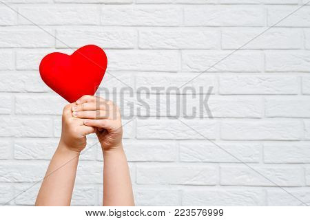 photo of a red heart which is holding hands