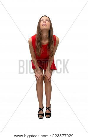 Sexy happy laughing girl in red dress in stockings and in high heels shoes is bending her knees and is looking up isolated on white background.