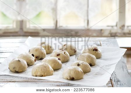 Raw unbaked buns. Ready to bake homemade Easter traditional hot cross buns on baking paper over white wooden table with window at background. Natural day light. Rustic style.