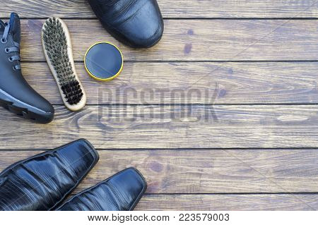 different men's black shoes with laces. shoe polish and a new shoe brush. on a wooden background. view from above. place for inscription