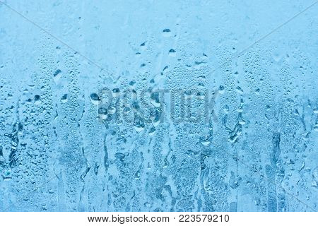 High level of humidity. Condensation drops pouring down the glass windows. Bad ventilation of the room.