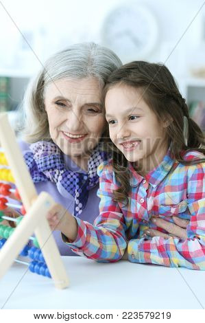 Grandmother teaching her granddaughter to use abacus indoors