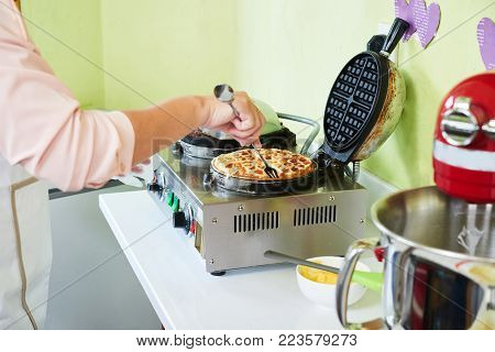 Woman taking fresh waffle out of waffle maker