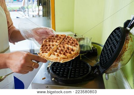 Woman taking freshly baked Belgian waffle out of waffle maker