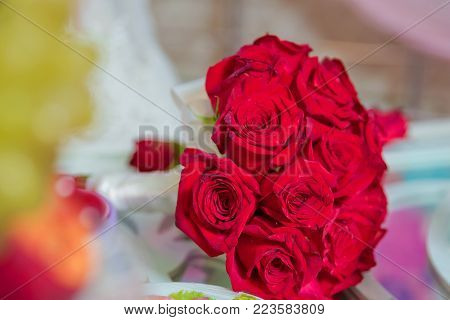 Red wedding bouquet of flowers . Wedding bouquet with pearls and red tapes . Wedding bouquet made of red Roses and Carnation flowers .
