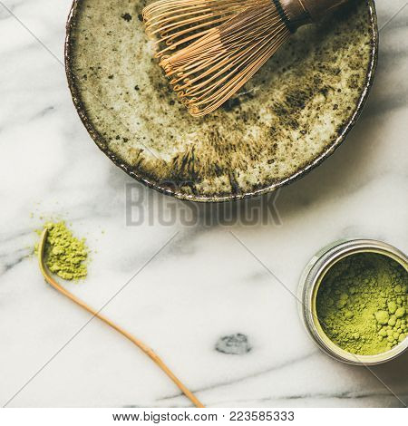 Flat-lay of Japanese tools for brewing matcha tea. Matcha powder in tin can, Chashaku spoon, Chasen bamboo whisk, Chawan bowl, cups for ceremony, grey background, top view, copy space, square crop