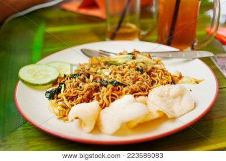 Asian cuisine - noodles in sauce with stir fried vegetables and fish chips. Bali island, Indonesia.