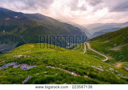 valley in Fagarasan mountains in afternoon. beautiful nature scenery on a cloudy summer day. view from the grassy hillside with footpath. part of Transfagarasan road is visible on the right slope
