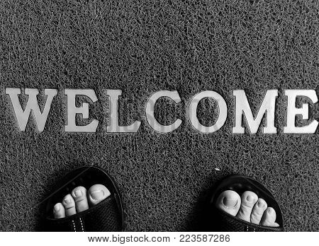 Closeup Black Mat With Welcome Word And Foot