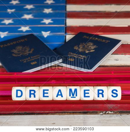 Dreamers children spelling letters on wooden USA flag with passports for citizenship