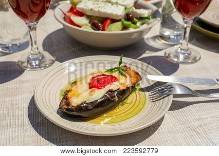 Papoutsakia stuffed eggplants dish of greek cuisine on white wooden table in greek tavern. Horizontal. Daylight. Close-up.