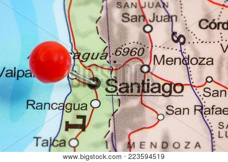 Close-up of a red pushpin in a map of Santiago, Chile.