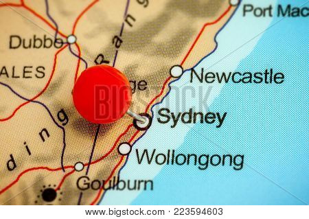 Close-up of a red pushpin on a map of Sydney, Australia.
