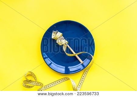 Medical starvation for lose weight. Empty plate, apple and measuring tape on bright yellow background top view.